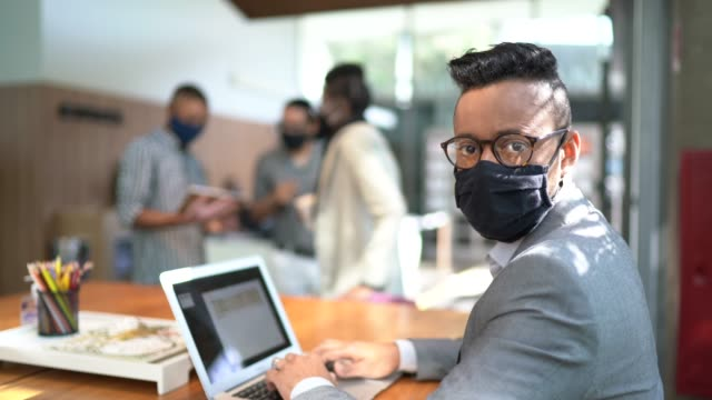 portrait of businessman using laptop at office's lobby - with face mask - businessman covid mask video stock e b–roll