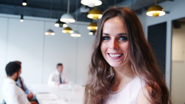 portrait of businesswoman in modern boardroom with colleagues meeting around table in background shot in slow motion - posizione fisica video stock e b–roll