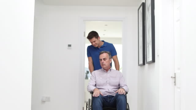 Portrait Of Carer Pushing Mature Man Using Wheelchair At Home Portrait Of Carer Pushing Mature Man Using Wheelchair At Home pushing wheelchair stock videos & royalty-free footage