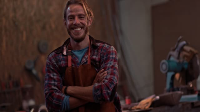 Portrait of carpenter standing in workshop with professional equipment Portrait of small business owner carpenter smiling and standing in industrial furniture manufacturing workshop carpenter stock videos & royalty-free footage