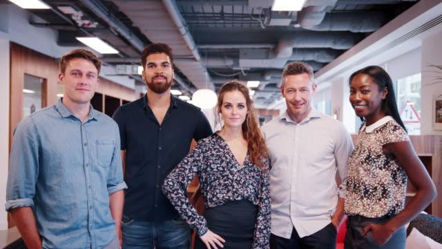 ritratto di uomini d'affari e uomini d'affari vestiti casualmente in moderno spazio ufficio girato al rallentatore - abbigliamento casual video stock e b–roll