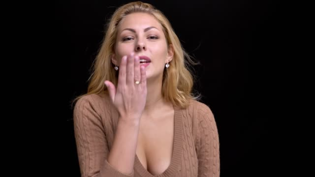 vidéos et rushes de portrait de baiser flirtingly soufflage caucasien femme aux cheveux longs en caméra sur fond noir. - décolleté