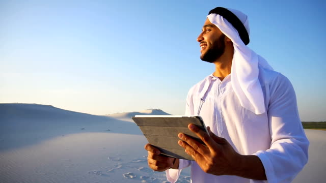 portrait of cheerful arab tourist who prints notes on gadget, standing among big desert on summer day - традиционная одежда стоковые видео и кадры b-roll