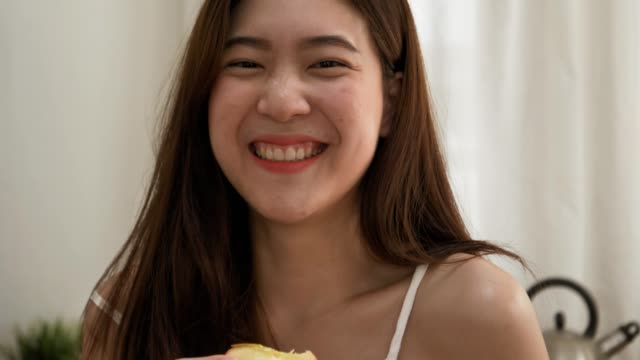 Portrait of cheerful asian woman eating green apple at home