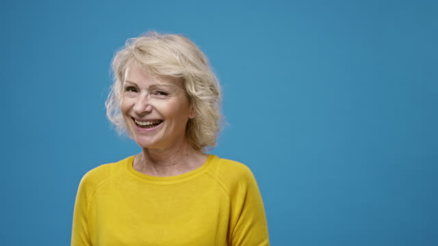 Portrait of Cheerful Caucasian Woman in Late 50s Slow motion video of smiling mature woman with medium-length blonde hair wearing yellow top with round neckline against blue background. background color stock videos & royalty-free footage