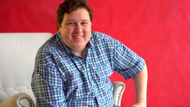 Portrait of cheerful fat man in plaid shirt playfully winking at camera over red background. video