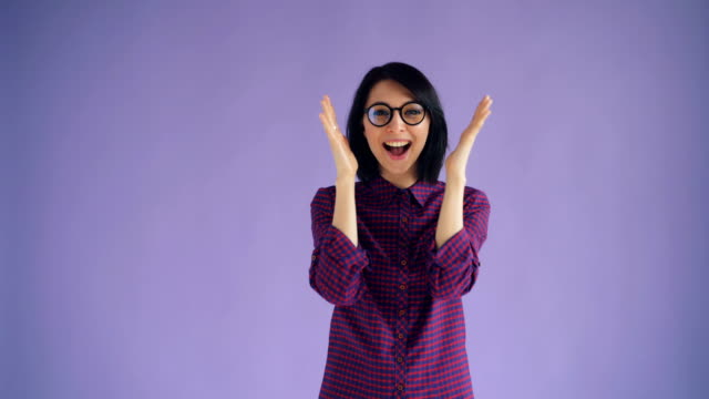 portrait of cheerful girl playing hide-and-seek smiling on violet background - donna si nasconde video stock e b–roll