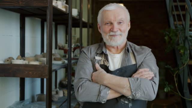 vídeos de stock, filmes e b-roll de retrato de ceramista sênior alegre em pé em oficina vestindo avental e sorrindo - cerâmica artesanato