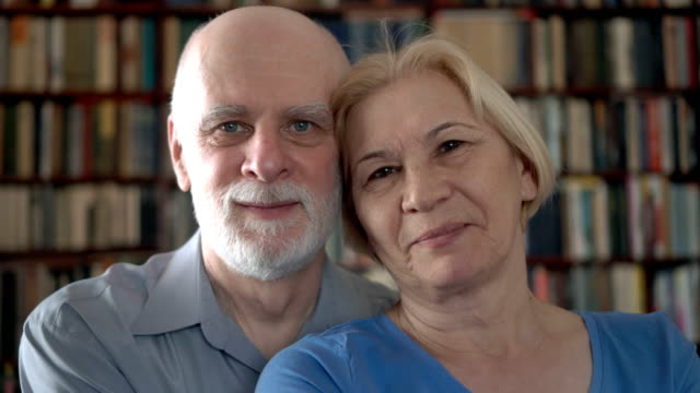 portrait of cheerful senior couple at home. having good time. bookcase bookshelves in background - couple portrait caucasian video stock e b–roll