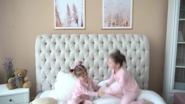 vídeos y material grabado en eventos de stock de retrato de niños saltando en una cama, niñas, dos hermanas se divierten y se ríen, niños felices en cuarentena, aislamiento de coronavirus en casa - hermana