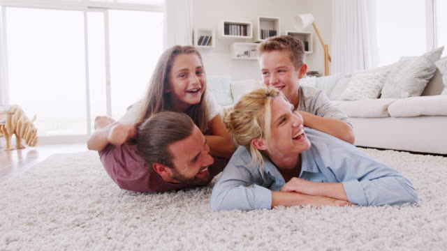 portrait of children lying on parents backs on rug in lounge at home shot in slow motion - tappeto video stock e b–roll