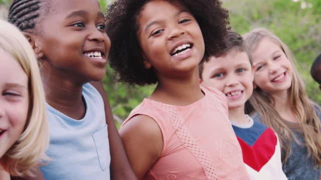 porträtt av barn som står på klätt ring frame med vänner i parken - multietnisk grupp bildbanksvideor och videomaterial från bakom kulisserna