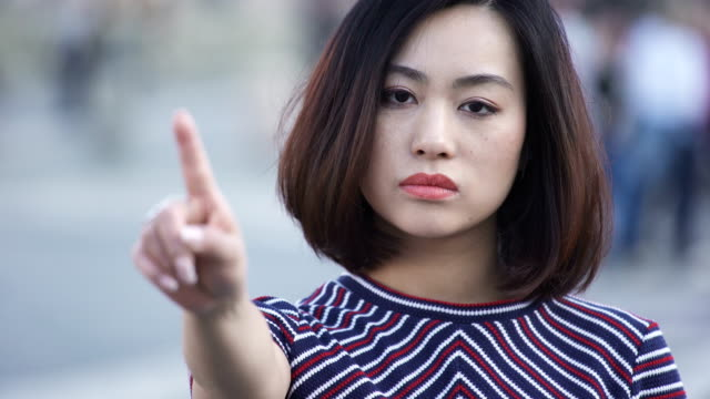 portrait of chinese serious woman says no with finger in the city street - furioso video stock e b–roll