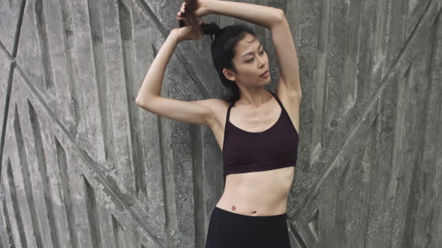 Portrait of Chinese woman with sport clothing tying her ponytail