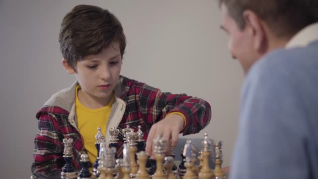 Portrait of concentrated Caucasian boy playing chess and showing victory gesture. His blurred grandfather at the foreground shaking his hand. Intelligent kid winning in competition. Lifestyle, hobby