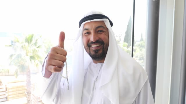 Portrait of Confident Arab businessman showing thumbs up in office