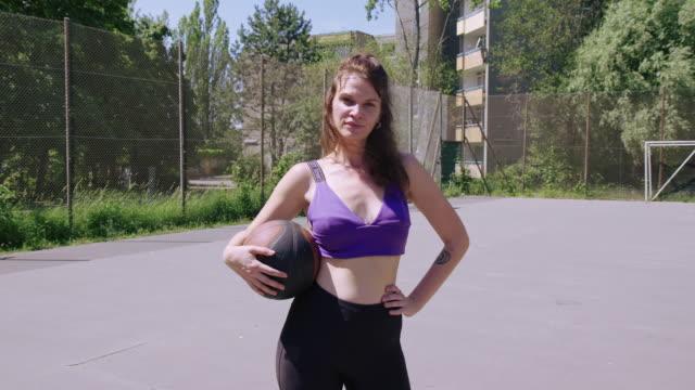 stockvideo's en b-roll-footage met portret van een zelfverzekerde basketbalspeler op de baan - handen op de heupen
