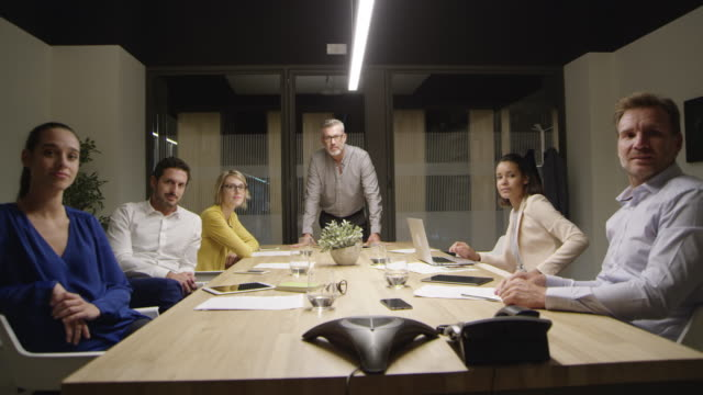 Portrait of confident business people in boardroom Dolly shot of confident business people in board room. Portrait of male and female professionals are at conference table. They are wearing formals. board room stock videos & royalty-free footage