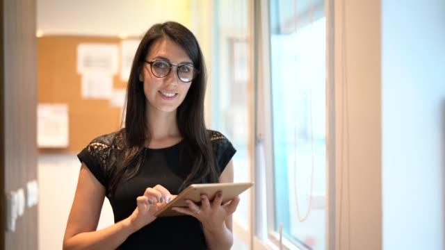 vídeos de stock, filmes e b-roll de retrato de mulher de negócios confiante usando tablet no escritório - brasileiro pardo