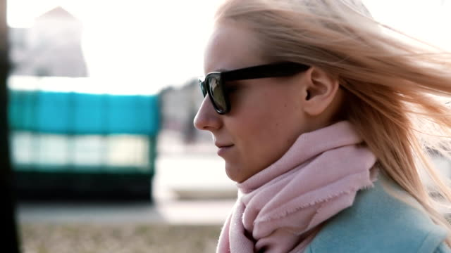 Portrait of confident Caucasian blonde girl 20s. Slow motion calm smiling young lady walking in stylish sunglasses video