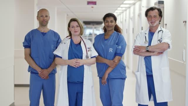 stockvideo's en b-roll-footage met portret van zelfverzekerde artsen in corridor in clinic - gezondheidszorg beroep