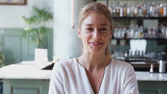 カウンターのそばに立っているレストランバーの自信に満ちた女性オーナーの肖像画 - 上半身点の映像素材/bロール