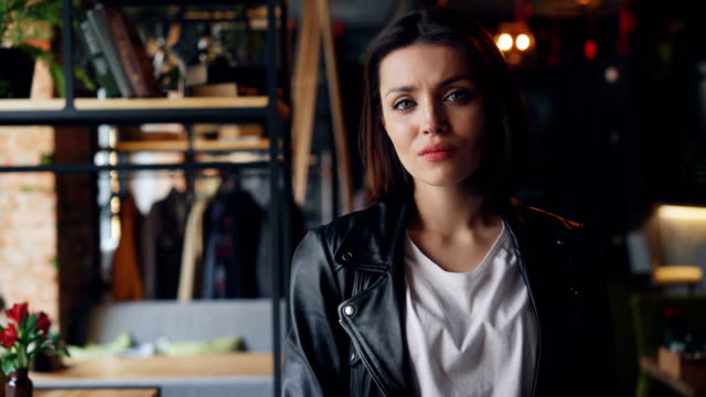 Portrait of confident girl hipster looking at camera standing in cafe alone Portrait of confident girl hipster looking at camera standing in cafe alone with serious face wearing cool clothing leather jacket and T-shirt. Millennials and emotions concept. charming stock videos & royalty-free footage