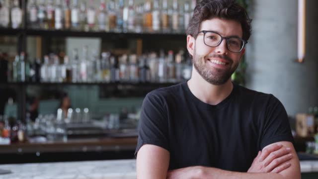 카운터에 의해 내부에 서 레스토랑 바의 자신감 남성 소유자의 초상화 - bartender 스톡 비디오 및 b-롤 화면