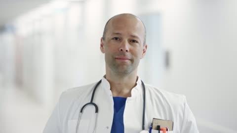 vídeos de stock e filmes b-roll de portrait of confident mature doctor at hospital - doutor