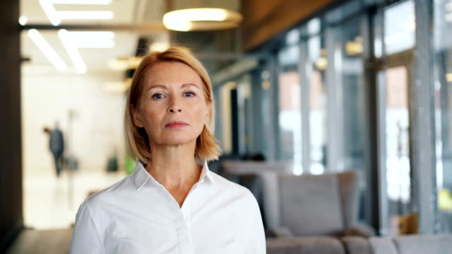 Portrait of confident mature woman looking at camera with straight face in cafe