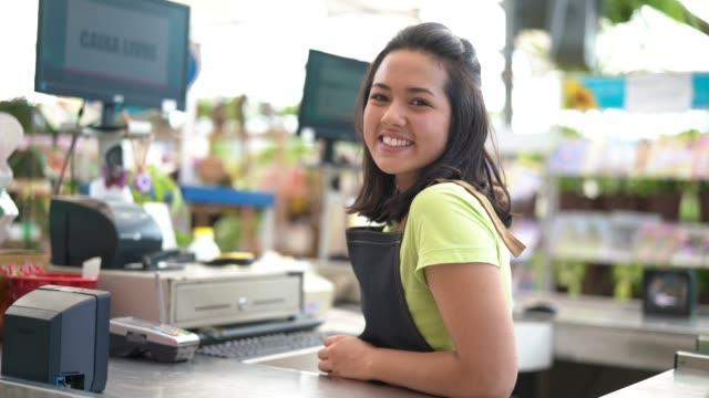 портрет уверенного владельца, опираясь на кассу в цветочном магазине - супермаркет стоковые видео и кадры b-roll