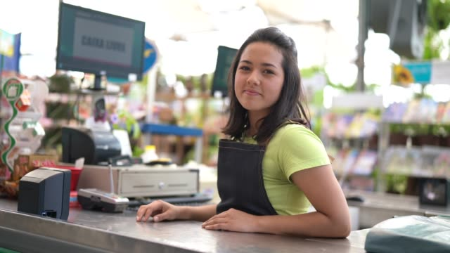 Portrait of confident owner leaning on checkout counter at flower shop Flower Shop saleswoman stock videos & royalty-free footage