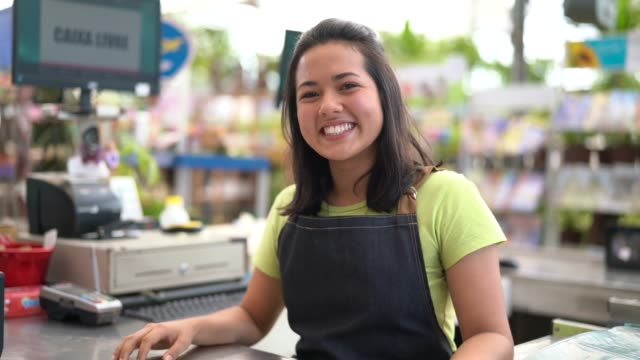 Portrait of confident owner leaning on checkout counter at flower shop Flower Shop satisfaction stock videos & royalty-free footage
