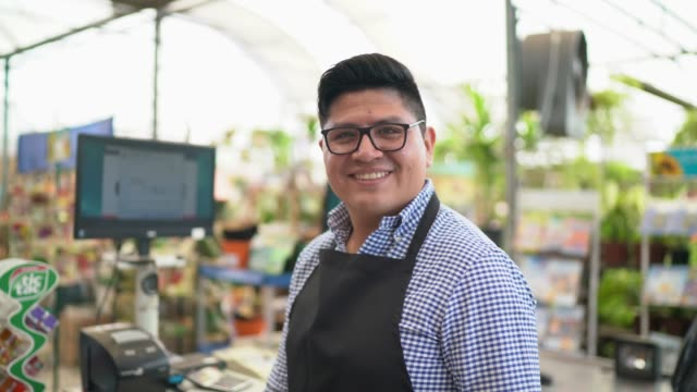 vídeos de stock e filmes b-roll de portrait of confident owner leaning on checkout counter at flower shop - supermarket worker