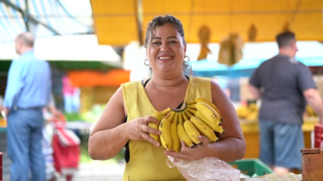 Portrait of confident owner - Selling bananas at farmers market Business owner saleswoman stock videos & royalty-free footage