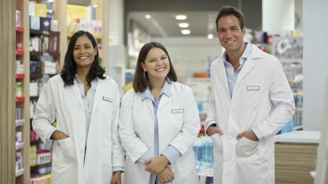 Portrait of confident pharmacists in drug store Handheld shot of happy chemists talking in drug store. Portrait of confident pharmacists with hands in pockets. Male and female chemists in lab coats at pharmacy. pharmacist stock videos & royalty-free footage