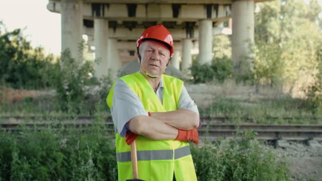 Portrait of confident senior railroader crossing hands at camera at railway video