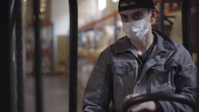 Portrait of confident serious Caucasian driver driving warehouse loader. Young handsome male employee in face mask working at factory storage on Covid-19 pandemic. Transporting, logistics. Portrait of confident serious Caucasian driver driving warehouse loader. Young handsome male employee in face mask working at factory storage on Covid-19 pandemic. Transporting, logistics. forklift stock videos & royalty-free footage