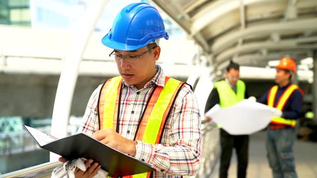 保護ヘルメットを身に着けている青写真を持って自信を持っての若いエンジニアの肖像画。 - 製造所点の映像素材/bロール