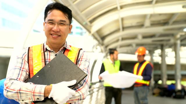 porträtt av självsäker ung ingenjör bär skyddande hardhat och håller blueprint. - kinesiskt ursprung bildbanksvideor och videomaterial från bakom kulisserna