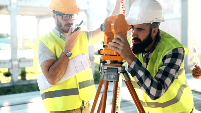 Portrait of construction engineers working on building site Portrait of construction engineers working on building site together survey stock videos & royalty-free footage