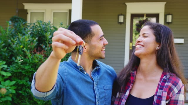 Portrait Of Couple Holding Keys To New Home On Moving In Day Portrait Of Couple Holding Keys To New Home On Moving In Day young couple stock videos & royalty-free footage