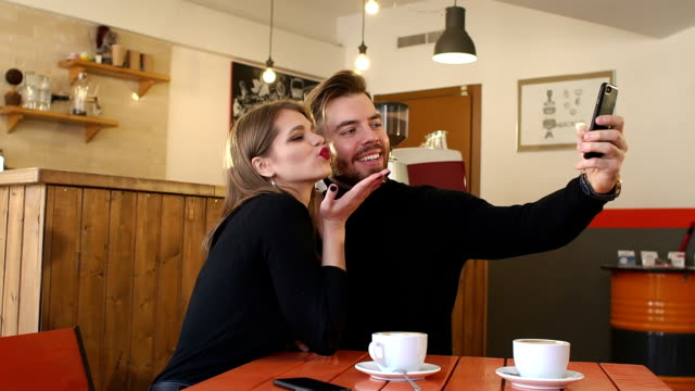 Portrait of couple in a cafe, they take a selfie and enjoy a fragrant cappuccino