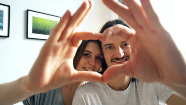 portrait of couple making heart with their hands looking at camera and smiling - mano donna dita unite video stock e b–roll