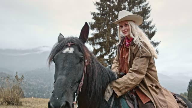 slo mo portrait of cowgirl stroking horse's neck - kowbojka praca związana z ziemią filmów i materiałów b-roll