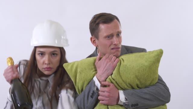 Retrato de pareja loco de cerca. Hombre tiene almohadilla, mujer en casco bailando con botella - vídeo