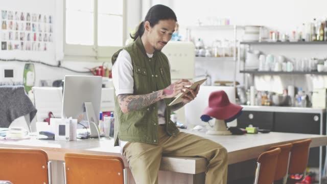 vídeos y material grabado en eventos de stock de retrato del creativo diseñador de moda japonés con tableta digital - moda preppy