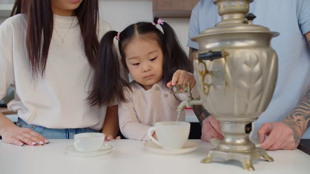 Portrait of cute asian baby girl pouring tea from samovar