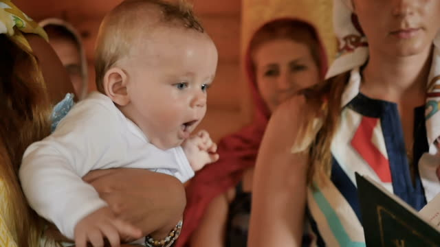 Portrait of cute baby in godmother hands during baptism ritual video