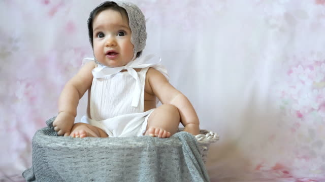 Portrait of cute baby  in retro style sitting in a basket indoors